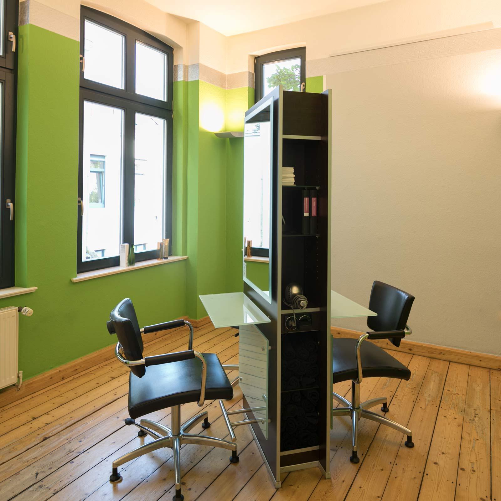 Ein ruam mit grüner Wand sowie zwei gegenüberstehenden Stühlen und Spiegeln dazwischen